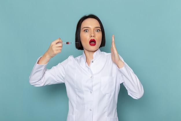 Une vue de face jeune infirmière en costume médical blanc s'injectant sur le médecin de l'hôpital de médecine de bureau bleu