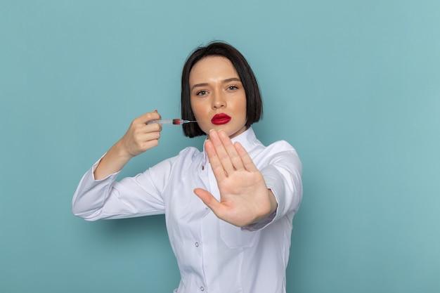 Une vue de face jeune infirmière en costume médical blanc et stéthoscope bleu s'injectant sur le médecin de l'hôpital de médecine de bureau bleu
