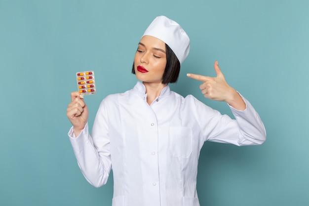 Une vue de face jeune infirmière en costume médical blanc et stéthoscope bleu tenant des pilules colorées