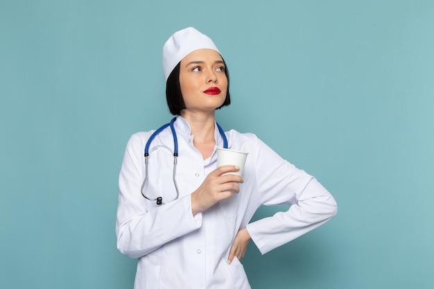 Une vue de face jeune infirmière en costume médical blanc et stéthoscope bleu tenant un verre en plastique sur le bureau bleu médecin de l'hôpital de médecine