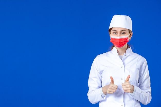 Vue de face de la jeune infirmière en costume médical avec masque rouge sur bleu
