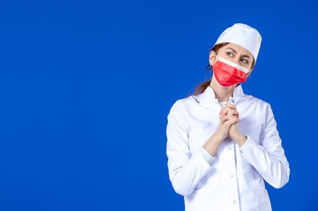 Vue de face jeune infirmière en costume médical avec masque rouge sur mur bleu