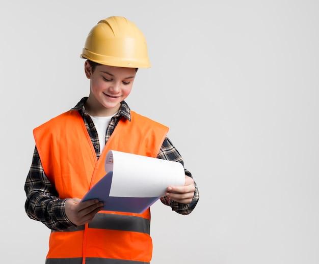 Vue de face jeune ingénieur lisant le plan de construction