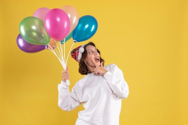 Vue de face jeune jolie femme tenant des ballons sur l'émotion de couleur jaune noël femme nouvel an