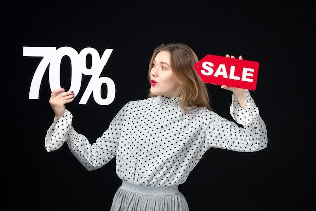 Vue de face jeune jolie femme tenant l'écriture de vente et sur les couleurs du mur noir shopping mode photo émotion modèle de beauté noël