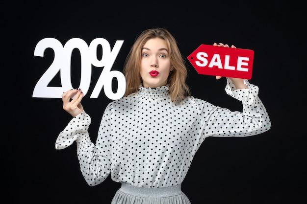 Vue de face jeune jolie femme tenant l'écriture de vente et sur le mur noir femme modèle émotion shopping couleur mode