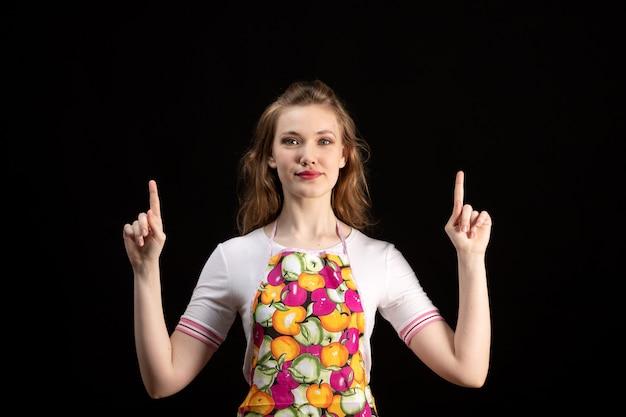 Une vue de face jeune jolie fille en cape colorée montrant des expressions de doigt sur le fond noir femme au foyer de nettoyage