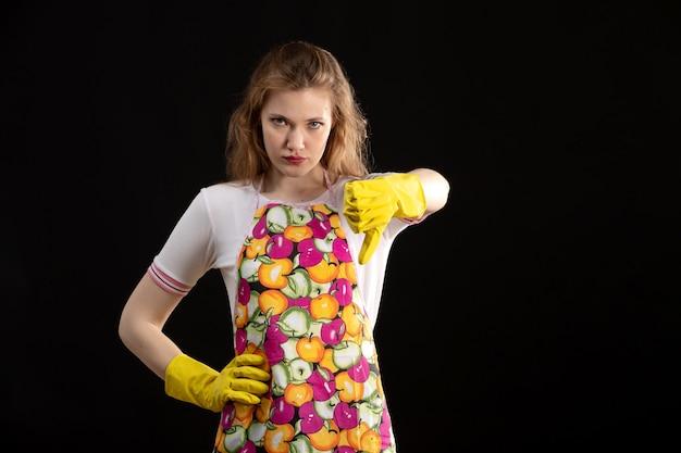 Une vue de face jeune jolie fille en cape colorée souriant portant des gants jaunes montrant un mauvais signe sur le fond noir amour sourire positivité