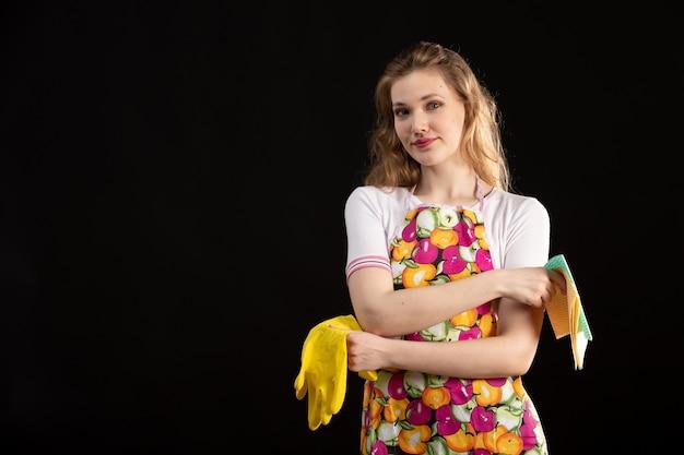 Une vue de face jeune jolie fille en cape colorée souriant tenant des gants de nettoyage sur le fond noir femme au foyer de nettoyage