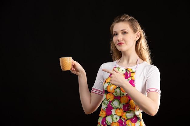 Une vue de face jeune jolie fille en cape colorée tenant une tasse orange sur le fond noir femme au foyer de nettoyage
