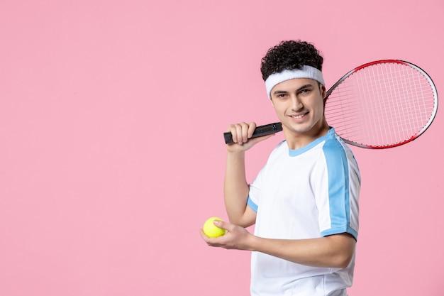 Vue de face jeune joueur de tennis en raquette de vêtements de sport sur mur rose