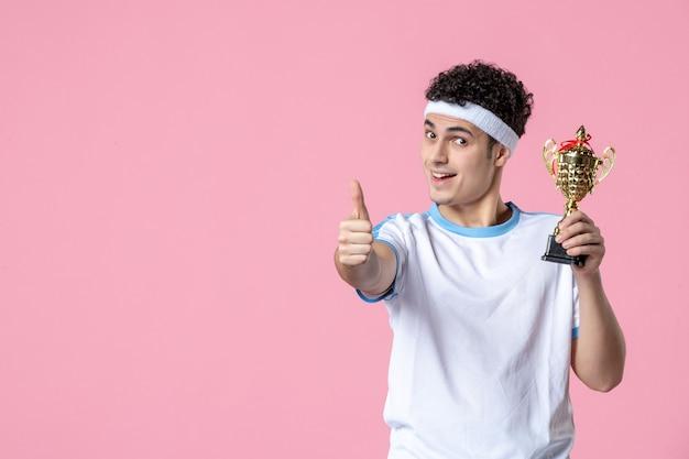Vue de face jeune joueur en vêtements de sport avec coupe d'or sur mur rose