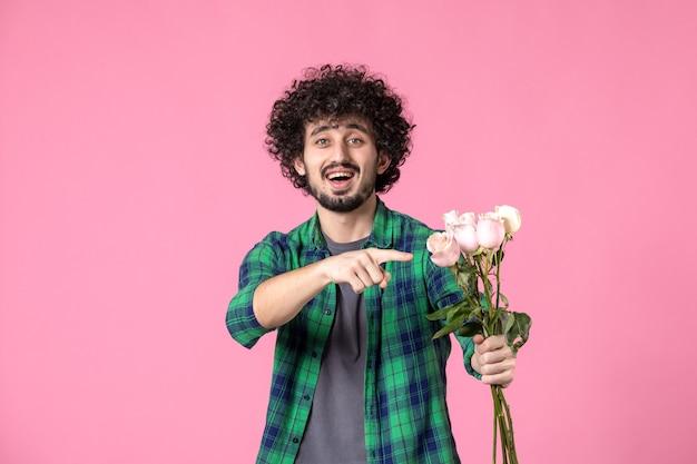 Vue de face jeune mâle avec des roses roses sur colorr rose