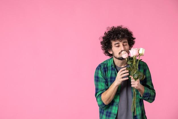 Vue de face jeune mâle avec des roses roses sur rose