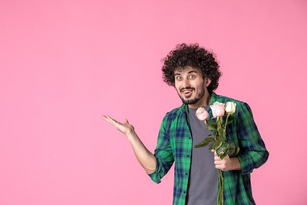 Vue de face jeune mâle avec des roses roses sur des roses
