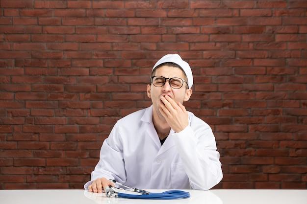 Vue de face jeune médecin béant en costume médical blanc sur mur de briques marron