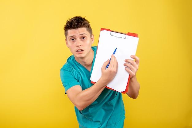 Vue de face jeune médecin de sexe masculin en costume médical avec des notes sur fond jaune