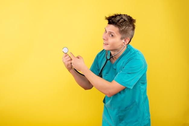 Vue de face jeune médecin de sexe masculin en costume médical avec stéthoscope sur bureau jaune