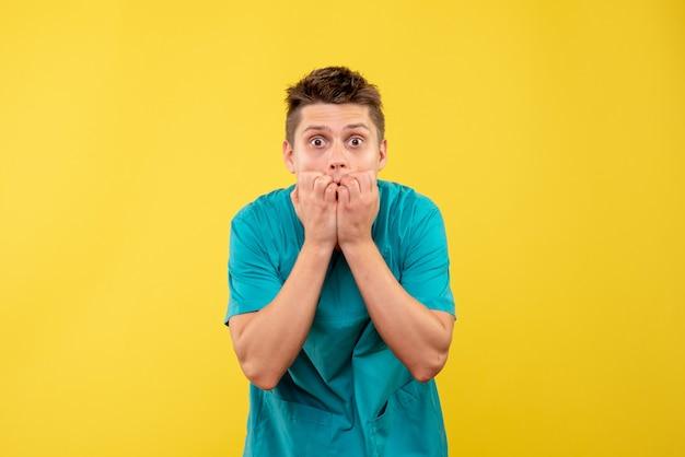 Vue de face jeune médecin de sexe masculin en costume médical surpris sur fond jaune