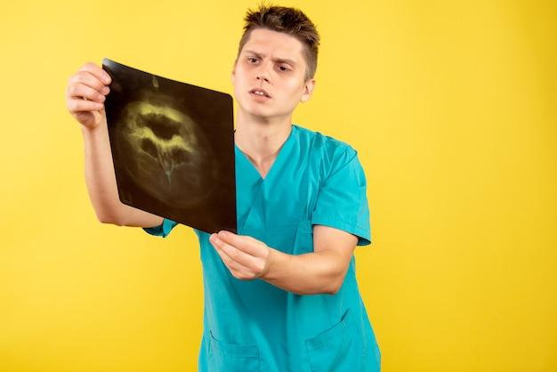 Vue de face jeune médecin de sexe masculin en costume médical tenant x-ray sur jaune