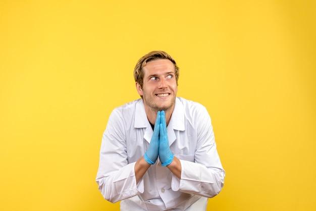 Vue de face jeune médecin de sexe masculin excité sur fond jaune pandémie de covid médicale humaine