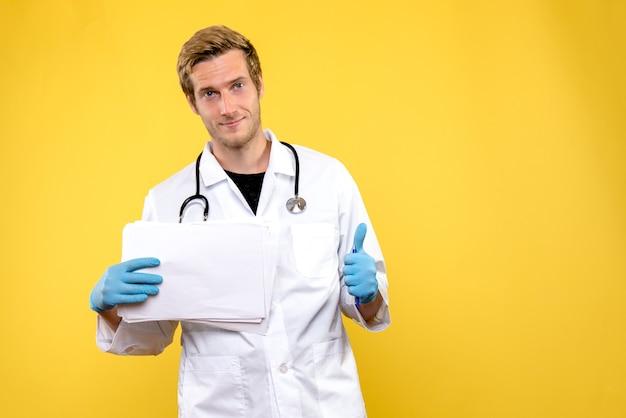 Vue de face jeune médecin de sexe masculin tenant des analyses sur fond jaune médecin de la santé de l'hôpital