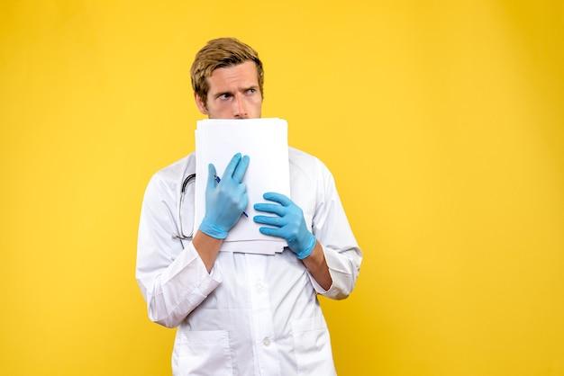 Vue de face jeune médecin de sexe masculin tenant des analyses sur fond jaune virus humain médical de la santé