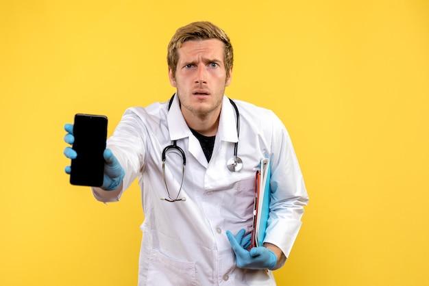 Vue de face jeune médecin de sexe masculin tenant le téléphone sur fond jaune virus humain médical de la santé