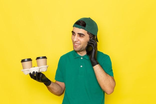 Vue de face jeune messager en chemise verte cap vert tenant des tasses à café et parler au téléphone sur jaune