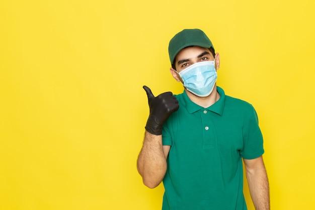 Vue de face jeune messager en chemise verte casquette verte gants noirs showign génial signe sur jaune