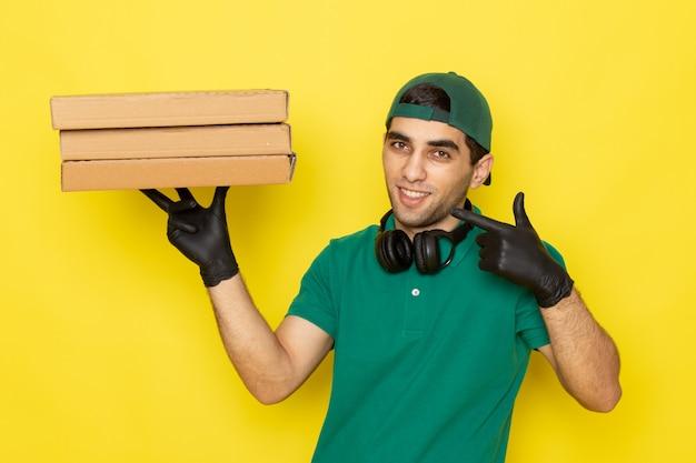 Vue de face jeune messager en chemise verte casquette verte gants noirs tenant des boîtes de livraison avec sourire sur jaune
