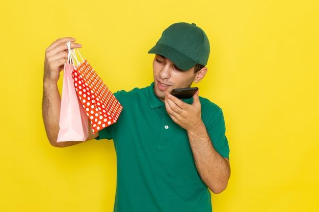 Vue de face jeune messager en chemise verte casquette verte parler au téléphone et petits paquets commerciaux sur le fond jaune offrant la couleur du service
