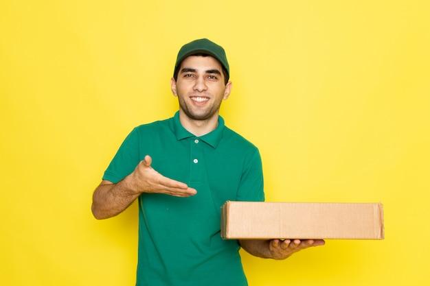 Vue de face jeune messager en chemise verte casquette verte souriant et tenant la boîte de livraison pointant dans la boîte de livraison sur le fond jaune offrant la couleur du service