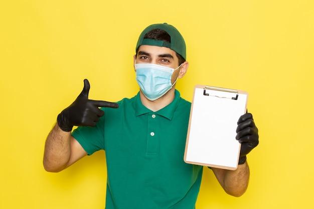 Vue de face jeune messager en chemise verte casquette verte tenant le bloc-notes sur jaune