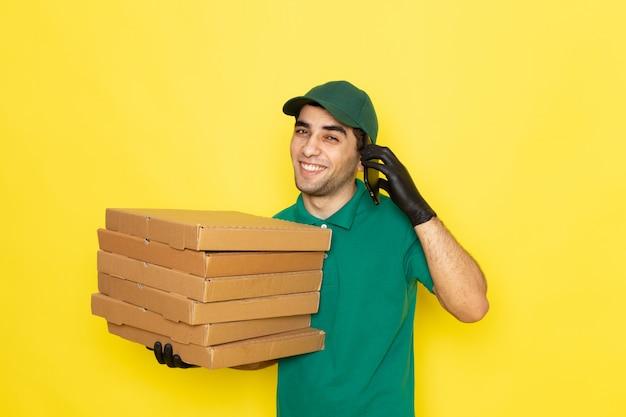 Vue de face jeune messager en chemise verte casquette verte tenant les boîtes de livraison et parler au téléphone sur jaune