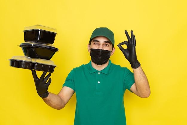 Vue de face jeune messager en chemise verte casquette verte tenant des bols de nourriture