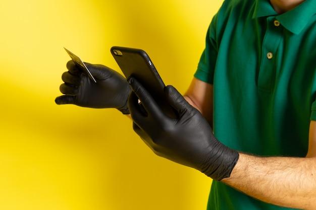 Vue de face jeune messager en chemise verte casquette verte tenant une carte blanche à l'aide de son smartphone sur jaune