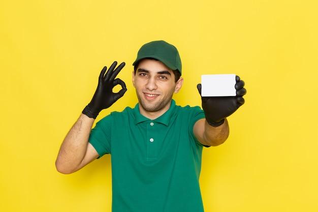 Vue de face jeune messager en chemise verte casquette verte tenant une carte blanche sur jaune