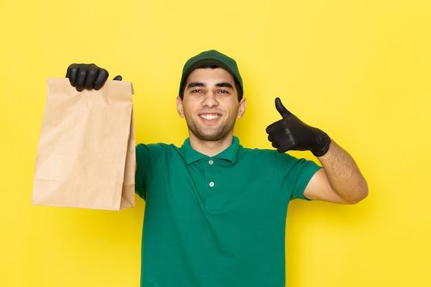 Vue de face jeune messager en chemise verte casquette verte tenant le colis de livraison sur jaune