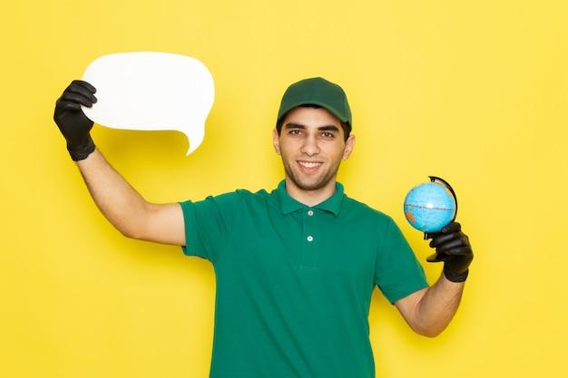 Vue de face jeune messager en chemise verte casquette verte tenant petit globe et panneau blanc avec des gants noirs sur jaune