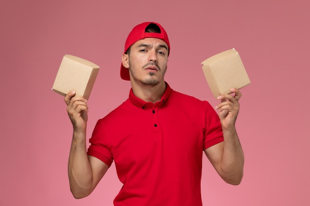 Vue de face jeune messager mâle en cape uniforme rouge tenant de petits paquets avec de la nourriture sur fond rose.