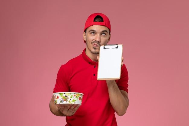 Vue de face jeune messager masculin en cape uniforme rouge tenant le bol de livraison rond et le bloc-notes pensant sur fond rose.