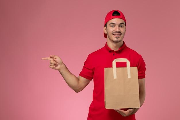 Vue de face jeune messager masculin en cape uniforme rouge tenant un paquet de papier alimentaire sur le fond rose.