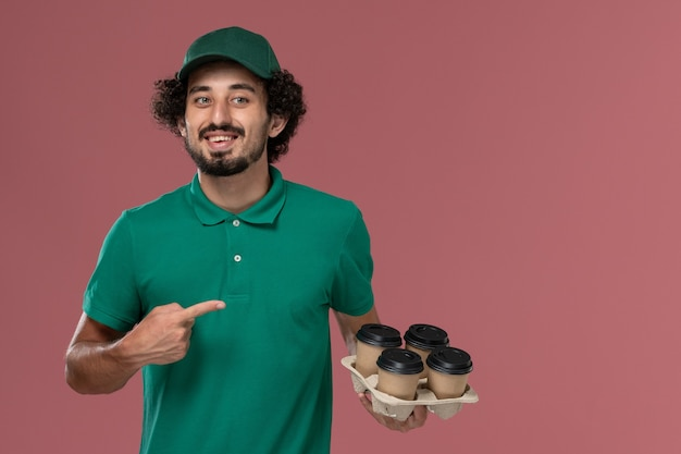 Vue de face jeune messager en uniforme vert et cape tenant des tasses de café de livraison marron et souriant sur fond rose clair service travail de livraison uniforme