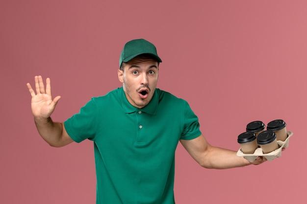 Vue de face jeune messager en uniforme vert tenant des tasses à café sur le fond rose