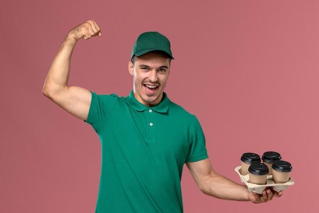 Vue de face jeune messager en uniforme vert tenant des tasses à café marron et fléchissant sur fond rose clair