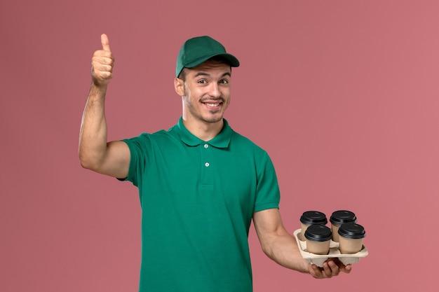 Vue de face jeune messager en uniforme vert tenant des tasses à café marron et souriant sur un bureau rose clair