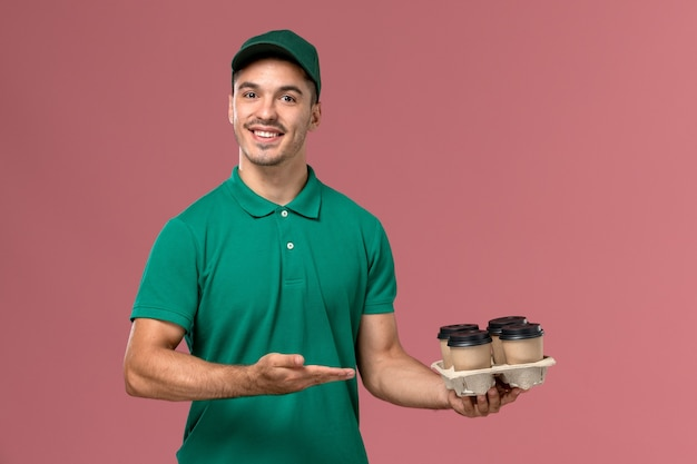 Vue de face jeune messager en uniforme vert tenant des tasses à café souriant sur fond rose clair