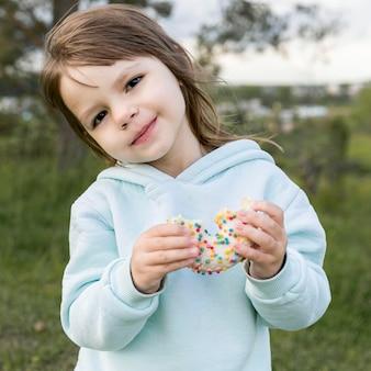 Vue de face jeune mignon manger un beignet