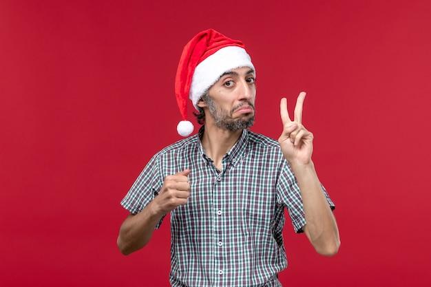 Vue de face jeune montrant le numéro sur le mur rouge vacances nouvel an mâle rouge
